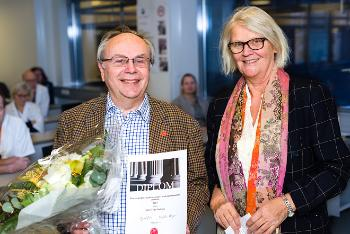 Jonn Terje Geitung holding diploma and flowers, flanked by Ingrid Os