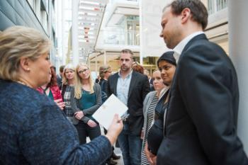 The picture shows Prime Minister Erna Solberg talking with PhD candidates and postdoctoral researchers from the faculty of medicine.