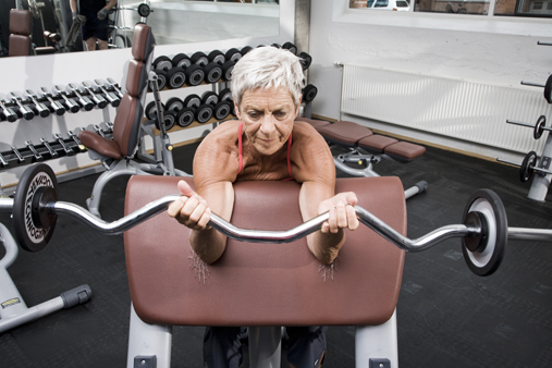 Elderly woman lifting weights at fitness center
