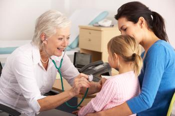 Lege på legekontor med en mor og et barn. Legen lytter på barnet,