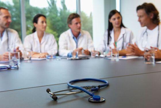 Fem unge leger i legefrakk rundt et bord, samtaler engasjert.