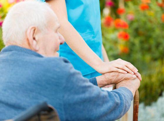 Eldre mann sitter ute, ryggen til og med stokk i hånden. Du ser en pleier stå ved ham og holder en betryggende hånd over hans.