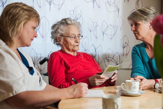 Sykepleier, kvinne på eldrehjem og pårørende