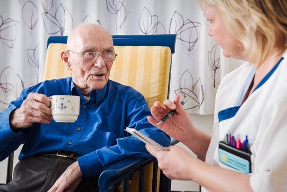 Eldre mann snakker med sykepleier