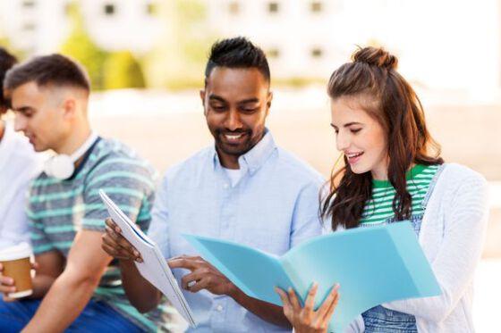 Tre studenter sitter utendlørs, permer i hånden.