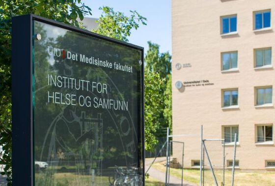 Skilt til Institutt for helse og samfunn, plassert i grønne omgivelser utenfor hovedbygget.