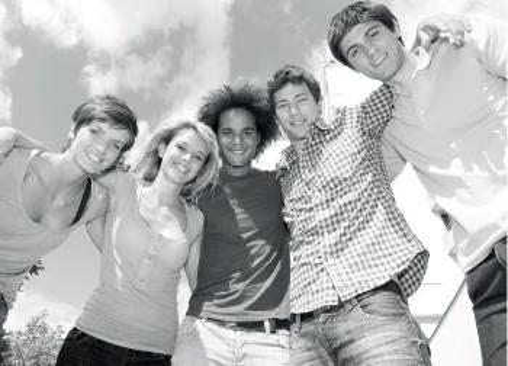 Svart-hvitt-bilde av fem studenter som smiler og støtter seg på hverandre - to unge kvinner og tre unge menn