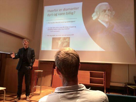 Førsteamanuensis Hans Olav Melberg står på scenen og snakker til forsamlingen på seminaret.
