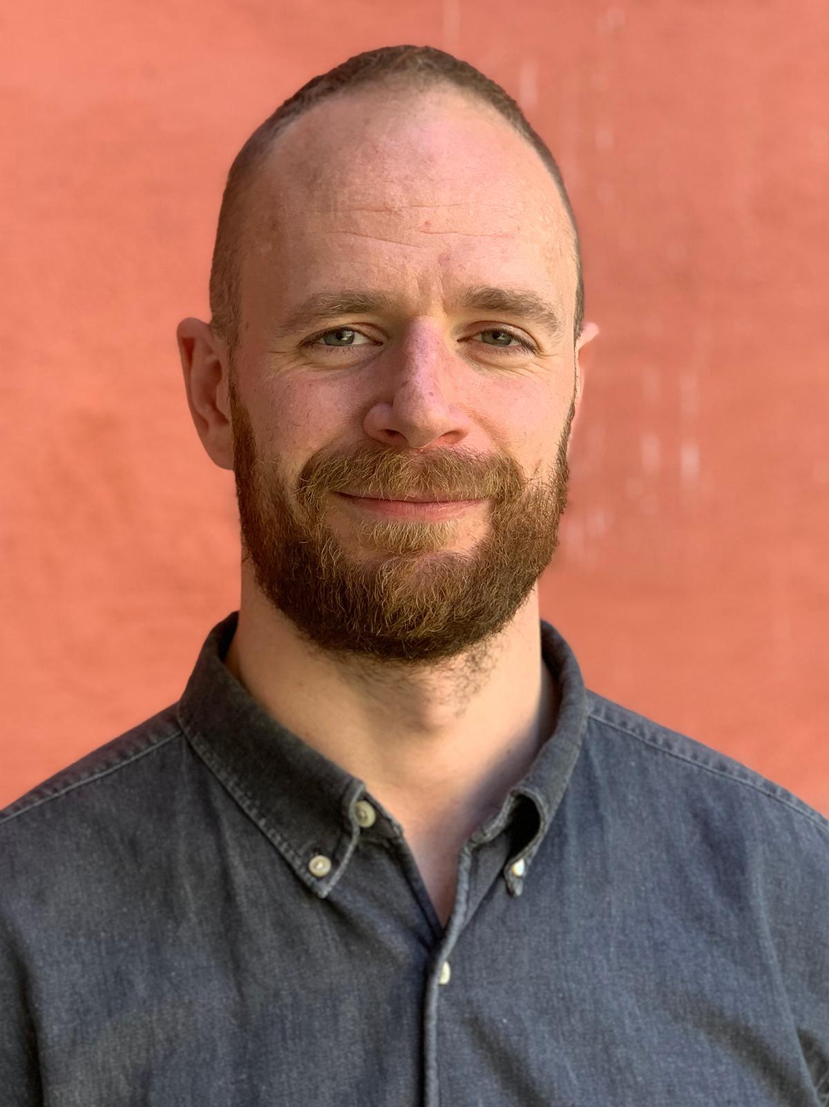 Mann i blå skjorte mot rød bakgrunn, forsiktig smil. Profilbilde Slagstad.
