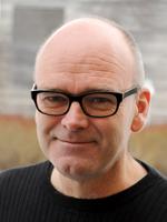 Profilbilde Per Haave - smilende mann, kledd i svart genser og med svarte markerte briller.