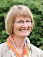 Profilbilde Hellesø. Smiler, halvlangt mellomblondt hår, briller, sommerskjerf, grønn bakgrunn