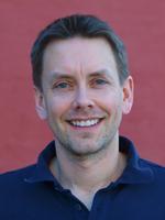 profilbilde Reidar Pedersen. Smiler, kort hår, blå skjorte, vinrød bakgrunn.