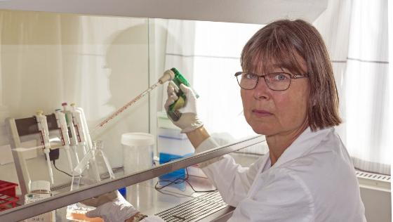 The picture shows a woman in a white lab coat who is holding lab equipment