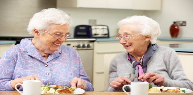 Two elderly women eating together in a kitchen