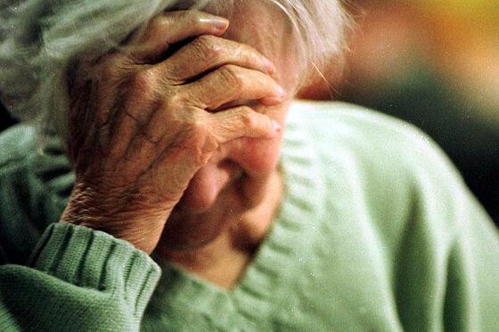 Eldre kvinne med hodet i hånda