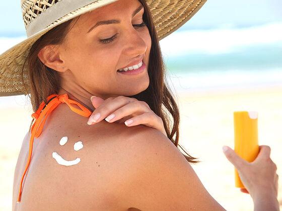 Kvinne smører seg inn med solkrem