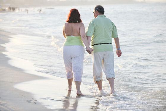 Mann og dame som vasser i strandkanten