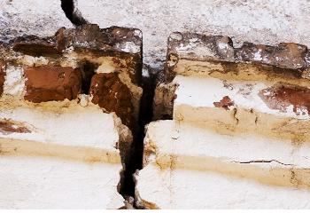 Close up image of a wall breaking down, with a crack running down the middle