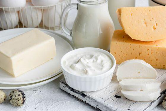 Foto av frokostbord med en mugge melk, noen oster, en bit smør og en skål med rømme.