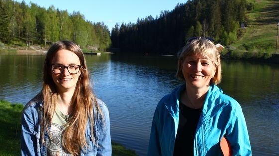 Bildet viser to kvinner som står foran et vann