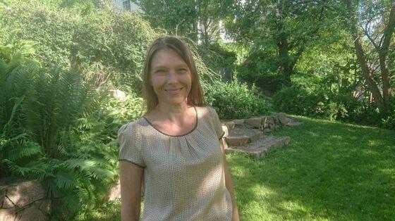 Bildet viser en kvinne med brunt, halvlangt hår som står i en hage.