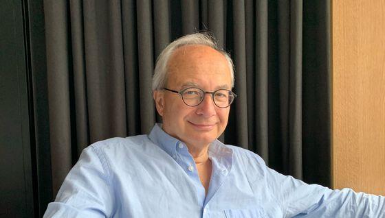 Bildet viser en mann med grått hår og briller som smiler mot kamera