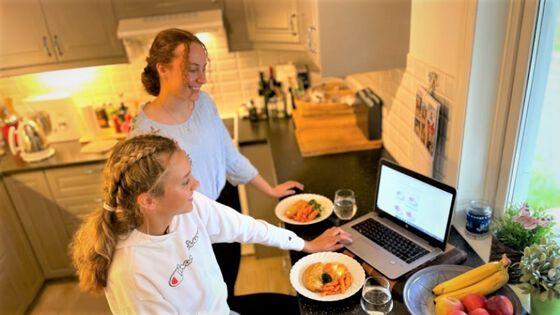 Bildet viser to jenter som sitter med mat foran en PC på et kjøkken