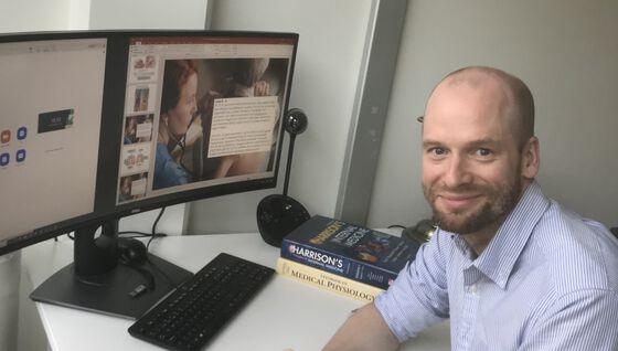 Bildet viser en mann som sitter foran en dataskjerm.