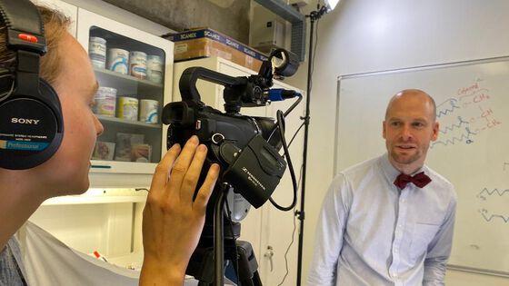 Bildet viser en mann som står foran et kamera og forklarer, mens en kvinne med hodetelefoner filmer