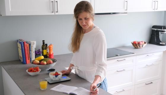 Bildet viser en kvinne på et kjøkken som veier mat og fører noe opp i en bok,