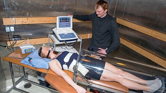 Bildet viser en kvinne som ligger på en benk med måleustyr på seg. Halve kroppen ligger inne i en tube. Det står en datamaskin ved siden av benken. En mann følger med.
