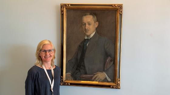 Bildet viser en kvinne med lyst hår og briller som står foran et maleri av en eldre mann i dress