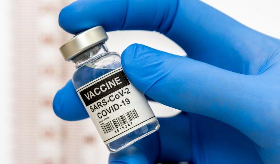 Image of a hand holding a glass containing COVID-19 vaccine.