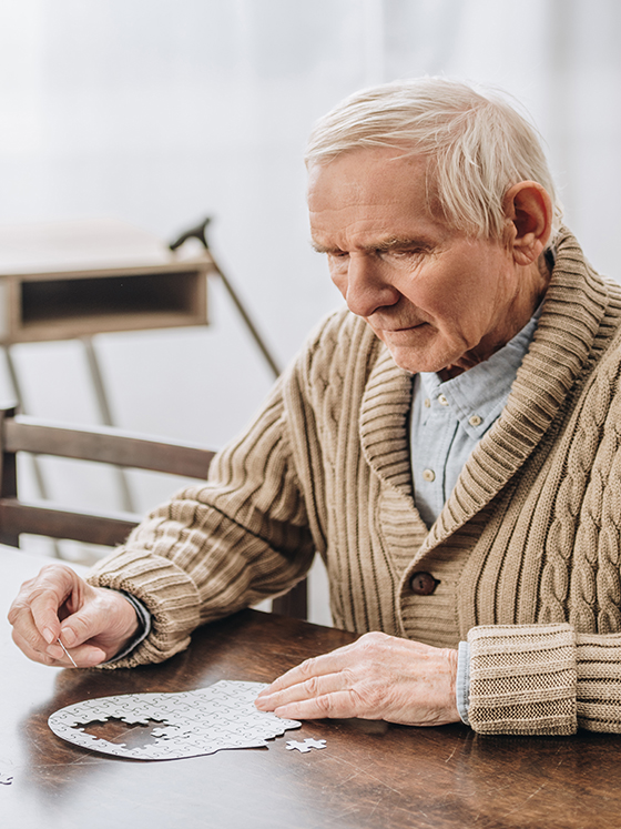 Eldre mann sittende ved et bord, ser bekymret ut