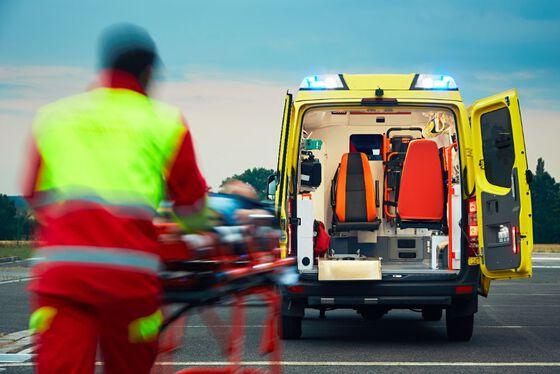 Bilde av ambulansearbeider og en ambulanse.