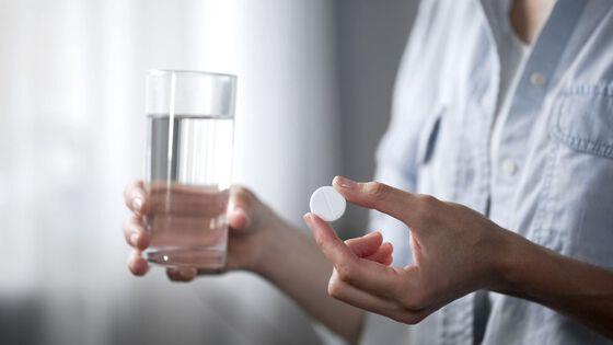 Bilde av en person som holder en pille og et vannglass.