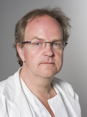 Portrettbilde av mann i hvit legefrakk.