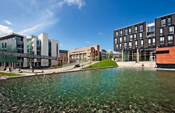 Photo of Oslo Science Park, showing the pond in front of the building on a sunny day