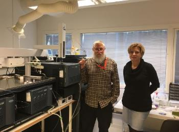 Photo of Dr Mayne and Dr Sekulic stood next to the HDX-MS instrument