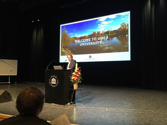 Photo of Oliver Billker opening the conference, standing on podium with screen behind