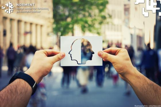Bildet viser to hender som holder opp en illustrasjon av et hode over en folkemengde