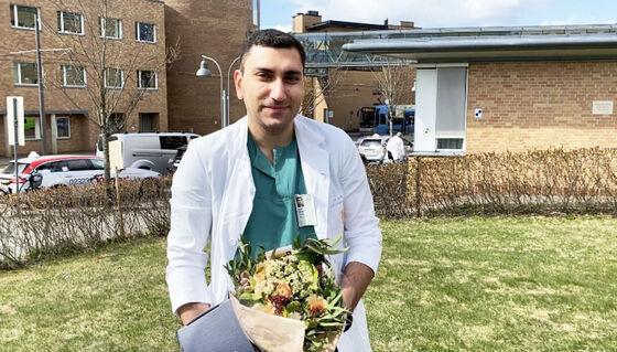Bildet viser en mann som holder blomster