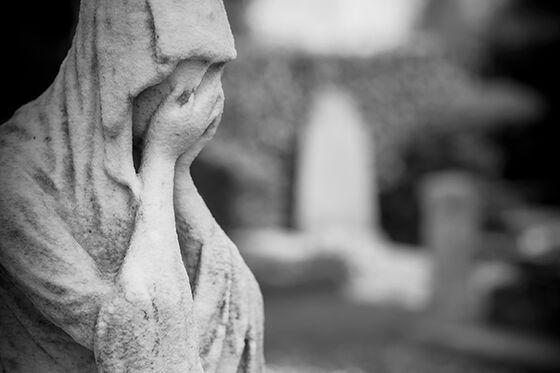 Statue av sørgende person. Svart-hvitt foto.