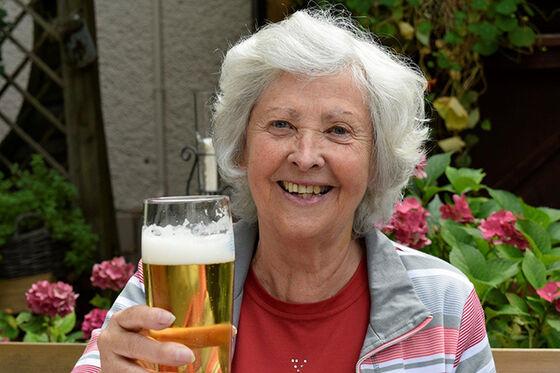 Fornøyd gråhåret dame med et glass øl.