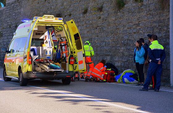En ambulanse som står i veikanten. Ambluansefolk og andre er på utsiden.