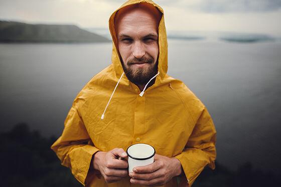 Mann i gul regnfrakk som holder en kaffekopp.