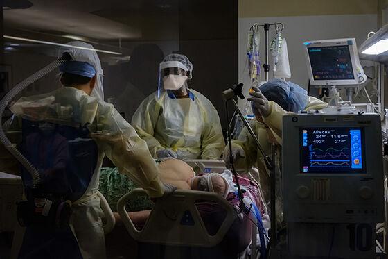 foto fra intensivenhet. Tre helsearbeidere i fullt smittevernutstyr og en pasient.