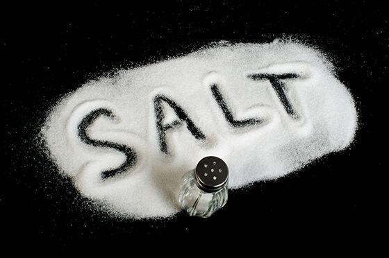 "the word ""salt"" written in white salt on a black tabletop"