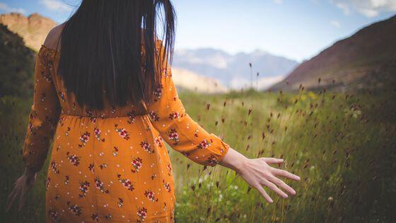 Kvinne som vandrer gjennom en eng av strå.