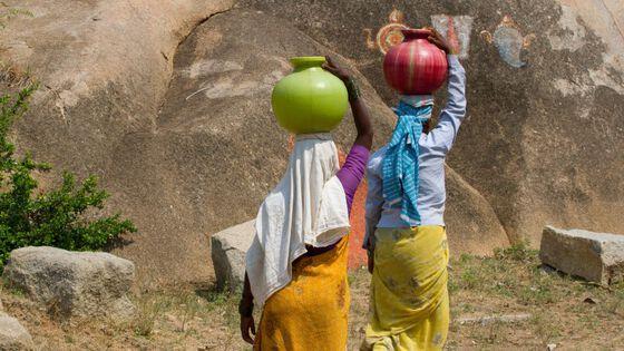 To kvinner som bærer vann på hodet.